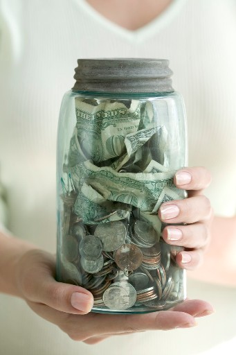 Woman holding a jar of coins and dollar bills